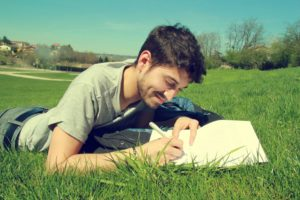 young man writing in field